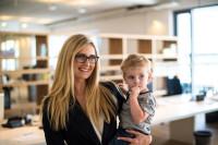 Berufstätige Frau mit Kind im Büro