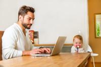 Home-Office: Vater arbeitet am Computer, Kind sitzt daneben