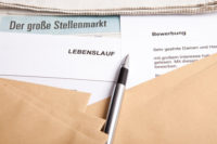 Stapel an Bewerbungen und der aktuelle Stellenmarkt